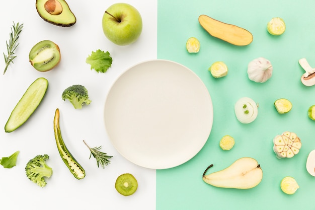 Piatto vuoto circondato da verdure e frutta