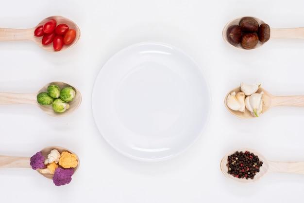 Piatto vuoto circondato da verdure nei cucchiai di legno su bianco
