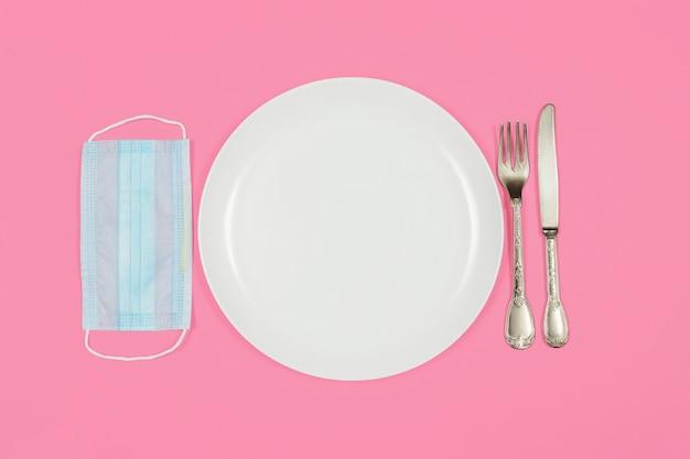 Piatto vuoto con forchetta e coltello e mascherina medica