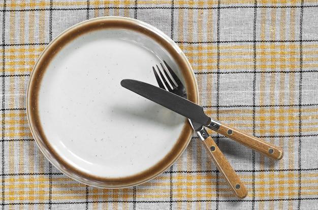 Piatto vuoto con forchetta e coltello su una tovaglia