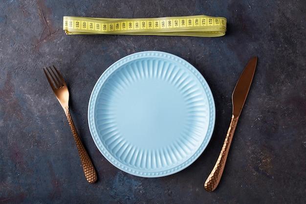 Piatto vuoto con forchetta e coltello vicino al nastro di misurazione. dieta per il concetto di perdita di peso. vista dall'alto