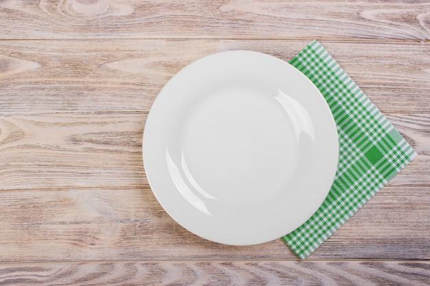 Piatto vuoto con il tovagliolo sulla tavola di legno grigia