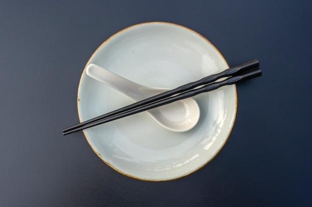 Piatto vuoto, cucchiaio e bacchette sulla tavola nera