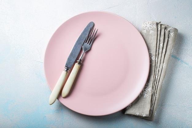 Piatto vuoto rosa con posate e asciugamano beige.