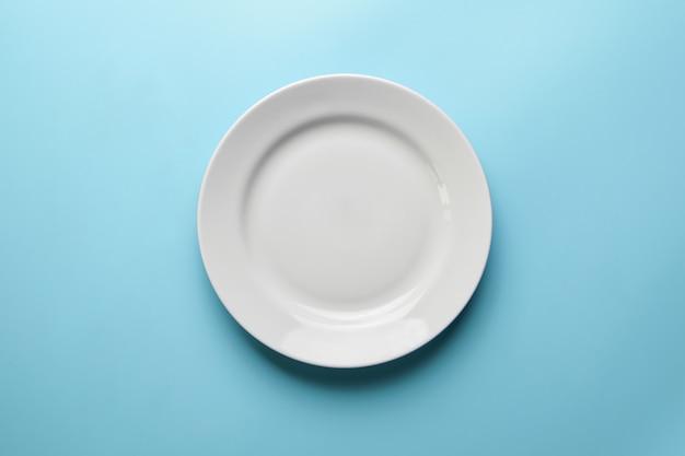 Piatto vuoto su sfondo blu, copia spazio. l'attività di ristorazione è fallita. il visitatore di un ristorante di lusso è in attesa di un ordine.