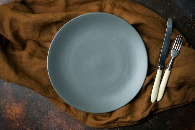 Piatto vuoto su uno sfondo scuro. svuoti il piatto ceramico grigio con un coltello e una forchetta per alimento e la cena su un bello fondo scuro.