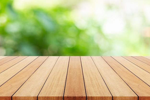Piatto vuoto sulla tavola di legno con fondo verde della sfuocatura. per il fotomontaggio
