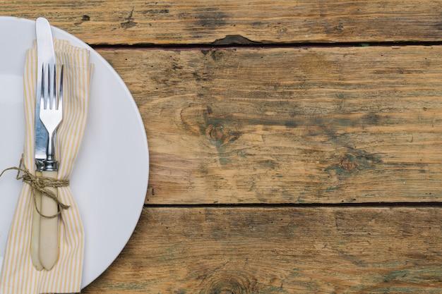 Piatto vuoto sulla vecchia tavola di legno con coltello, forchetta e tovagliolo