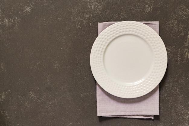 Piatto vuoto, tovagliolo tessile grigio su cemento nero