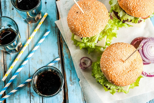 Pic-nic fast food cibo malsano hamburger gustosi freschi deliziosi con cotoletta di manzo verdure fresche e formaggio sul vecchio tavolo di legno blu rustico con acqua gassata dolce