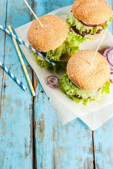 Pic-nic, fast food. cibo malsano. hamburger saporiti freschi deliziosi con la cotoletta di manzo