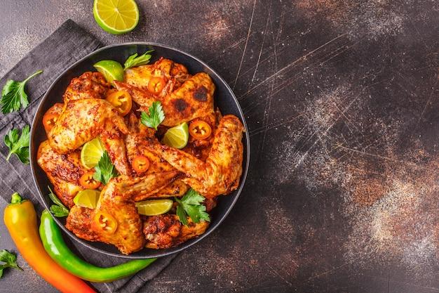 Piccante ali di pollo fritte in salsa di paprika in un piatto nero su uno spazio buio, vista dall'alto, copia dello spazio.