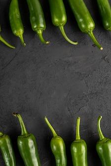 Piccante fresco fresco del peperone verde su fondo grigio