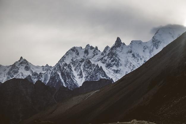 Picchi di montagna del massiccio innevati nella gamma di karakoram al tramonto