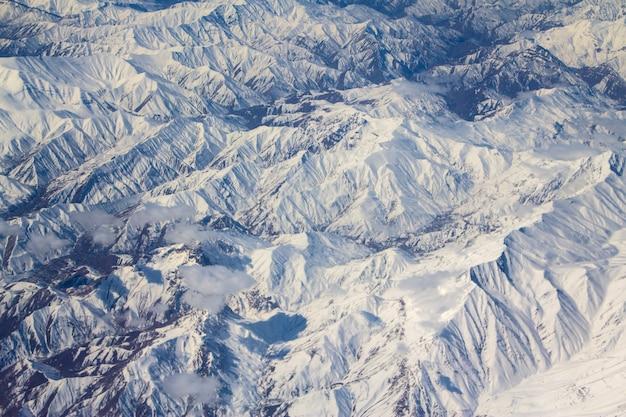 Picchi di montagna nella neve da un finestrino dell'aereo