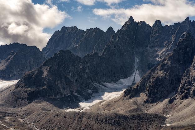 Picchi di montagna rocciosa con nuvole