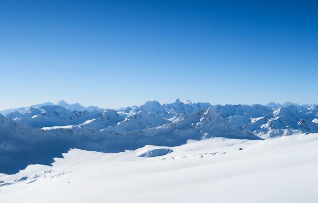 Picchi innevati delle montagne caucasiche nel cielo blu. regione di elbrus
