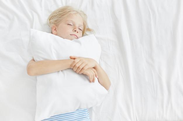 Piccola adorabile ragazza con i capelli biondi, la faccia lentigginosa, chiudendo gli occhi, abbracciando il cuscino bianco, dormendo piacevolmente sui vestiti da letto bianchi. bambino che ha sogni piacevoli nella mattina che riposa a casa