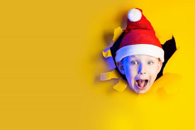 Piccola allegra babbo natale in cappello sorride, uscendo dallo sfondo giallo sfilacciato illuminato dalla luce al neon
