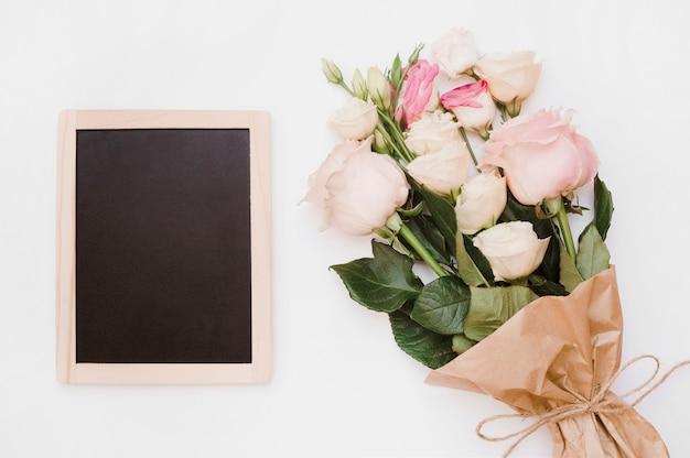 Piccola ardesia di legno vuota con bouquet di fiori su sfondo bianco