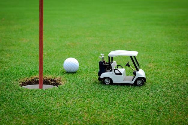 Piccola automobile del golf figura su verde