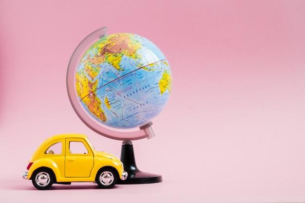 Piccola automobile retro gialla sveglia con la sfera del globo del mondo