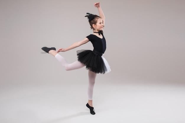 Piccola ballerina della neonata che balla in abbigliamento in bianco e nero che sorride avendo emozione positiva