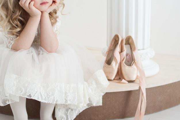 Piccola ballerina in abito bianco seduto accanto a scarpe da punta grandi
