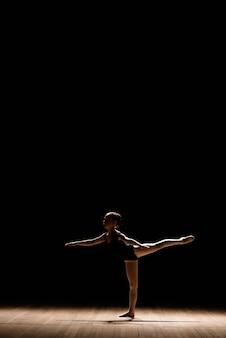 Piccola ballerina sveglia in costume di balletto scuro che balla sul palco. kid in classe di danza. la ragazza del bambino sta studiando la balletto.