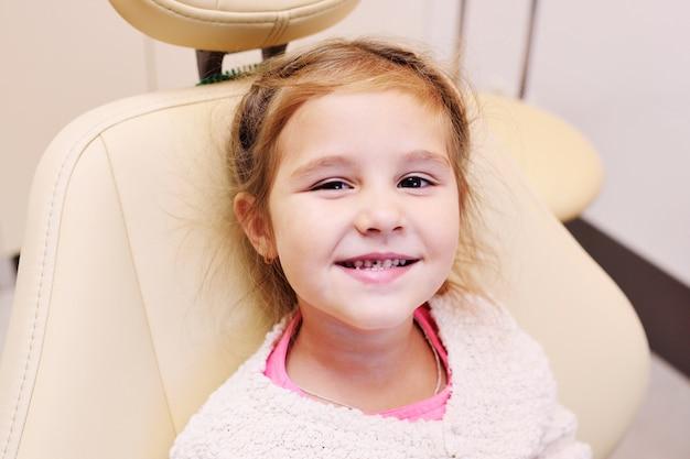 Piccola bambina con carie dentale sui denti nella sedia dentale sui denti nella poltrona del dentista