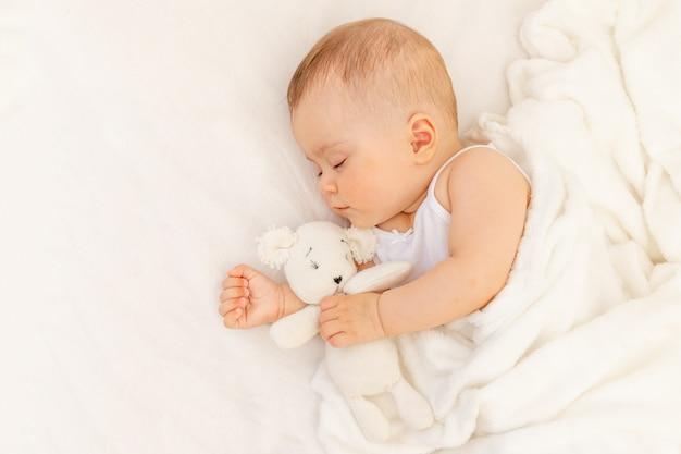 Piccola bambina di 6 mesi che dorme in un letto bianco, sonno sano del bambino
