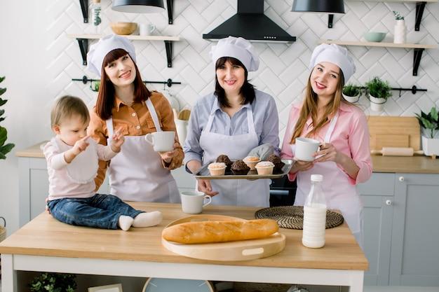 Piccola bambina è seduta sul tavolo in cucina e divertirsi. la nonna e le sue figlie bevono caffè e mangiano muffin. donne felici in grembiuli bianchi che cuociono insieme. festa della mamma