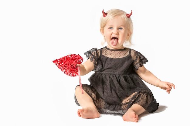 Piccola bambina in abito nero e corna da diavolo