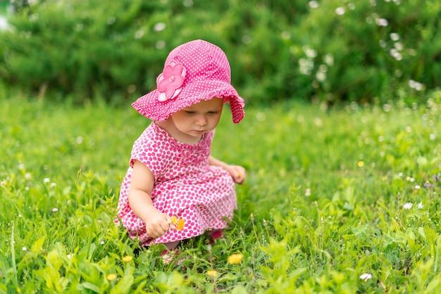 Piccola bambina in rosa accovacciata sul prato e raccogliere fiori
