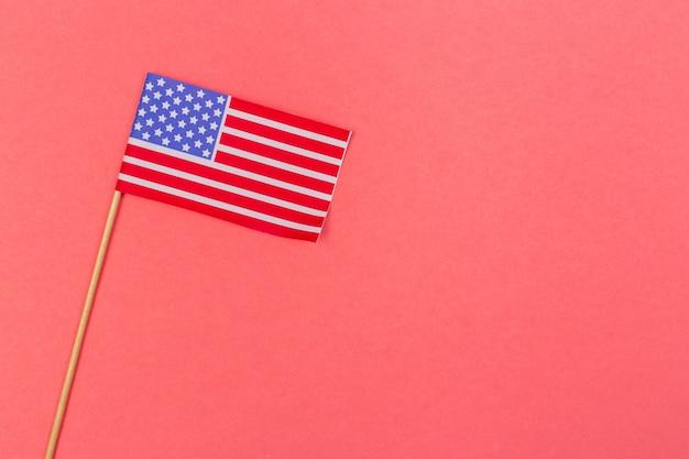 Piccola bandiera americana di carta sul bastone di legno su luminoso