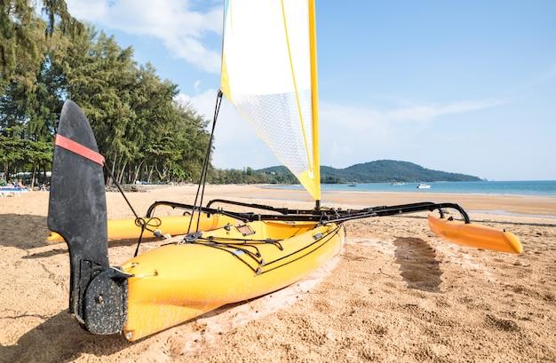 Piccola barca a vela del catamarano sulla riva alla spiaggia della tailandia