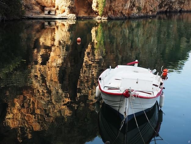 Piccola barca autentica nella baia con acqua blu