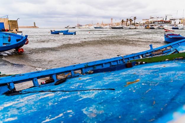 Piccola barca ormeggiata al porto di bari, in italia, durante una tempesta in mare.