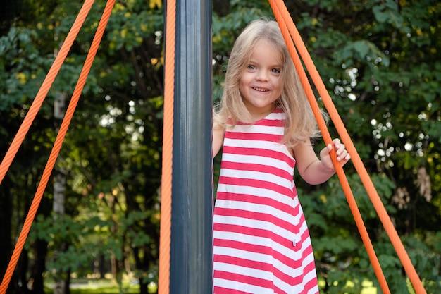 Piccola bella ragazza che gioca sulla giostra nel parco nel parco giochi.