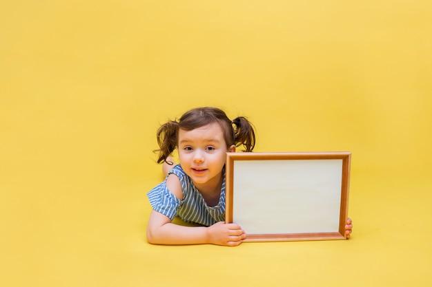 Piccola bella ragazza con le trecce con un'insegna per la pubblicità su un giallo isolato