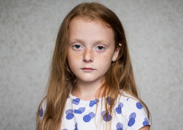 Piccola bella ragazza dai capelli rossi con le lentiggini che guarda seriamente