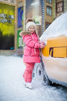 Piccola bella ragazza sui pattini vicino al taxi