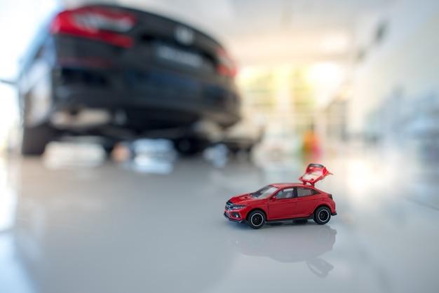 Piccola berlina rossa e rendiconto finanziario con monete finanza auto e prestiti, risparmia denaro per idee o materiali di design automobilistico