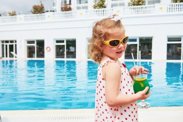 Piccola bionda sveglia in piscina e tenendo un cocktail per bambini.