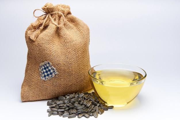 Piccola borsa di tela con semi di girasole e una ciotola di vetro con olio su uno sfondo bianco.
