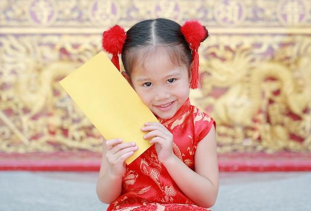 Piccola busta asiatica sorridente della holding dell'oro della ragazza