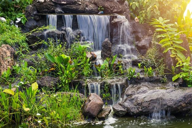 Piccola caduta artificiale dell'acqua nella decorazione dello spazio verde domestico del giardino del parco.