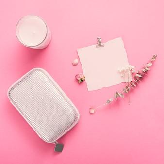 Piccola carta con rami, candela e pochette sul tavolo