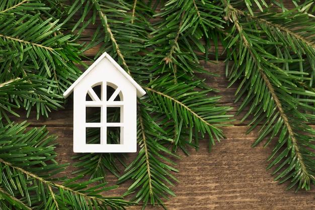 Piccola casa bianca su rami di abete, in legno.