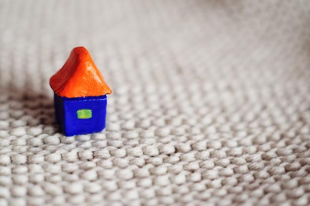 Piccola casa blu del giocattolo con un tetto arancione su una priorità bassa lavorata a maglia grigia